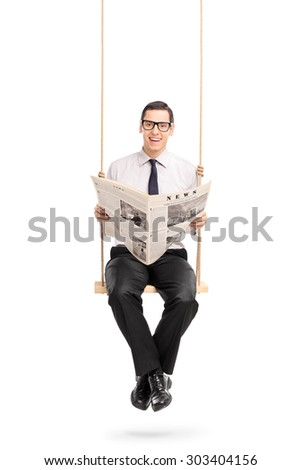 Vertical shot of a young man reading a newspaper seated on a swing and looking at the camera isolated on white background - stock photo