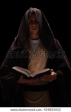 Vertical shot of a young monk reading a book on black background