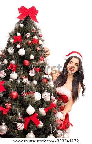 Vertical shot of a young woman in Santa costume posing behind a Christmas tree isolated on white background - stock photo