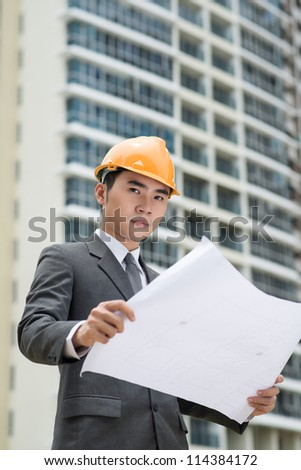 Vertical shot of an elegant business worker with a modern high-rise building in the background