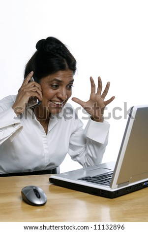 Vertical shot of an Indian woman at her laptop while on the phone
