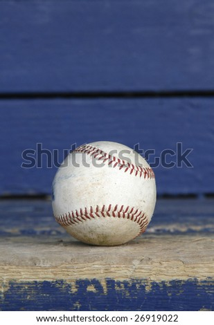vertical shot of an old baseball sitting on a dugout bench.