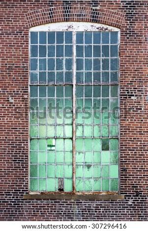 vertical shot of an old industrial window set in a brick wall