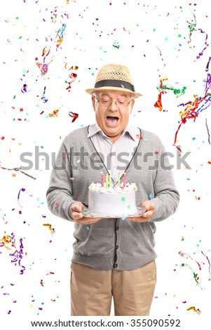Vertical shot of an overjoyed senior holding a birthday cake with confetti streamers flying around him isolated on white background