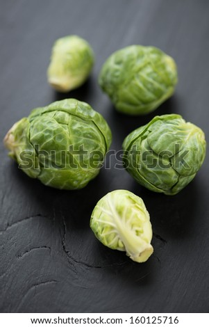 Vertical shot of brussels sprouts, dark wooden background - stock photo