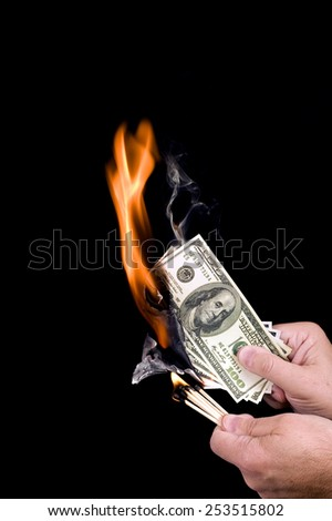 Vertical Shot Of Burning False Money/ Losing Money - stock photo