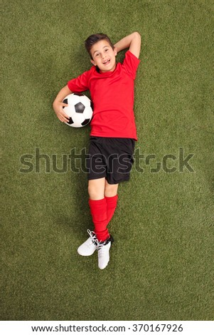 Vertical shot of carefree little boy in a football jersey laying on a grass field and holding a football - stock photo