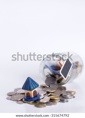 Vertical shot of coin spilling from coin jar,small house model and small chalkboard label