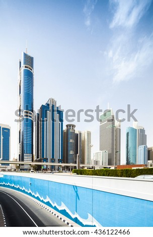 Vertical shot of Dubai skyline with blue tunnel