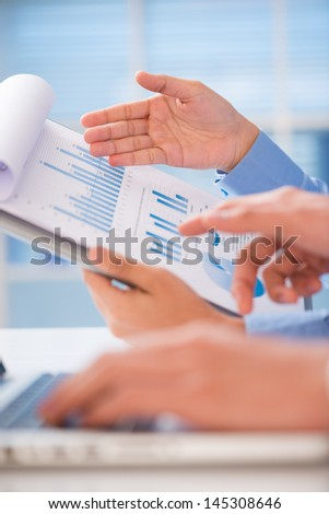 Vertical shot of human hands holding a folder with a diagram  - stock photo