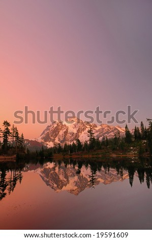Vertical shot of Mount Shuksan with the alpine glow after sunset from Picture Lake. - stock photo
