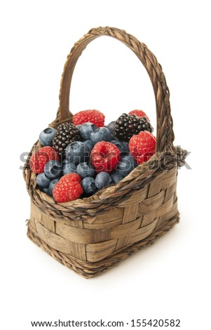 vertical shot of wicker basket filled with berries isolated on white