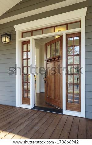 Vertical shot of wooden front door  of an upscale home with windows/Exterior shot of an open Wooden Front Door - stock photo