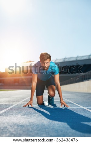 Vertical shot of young male runner taking ready to start position facing the camera. Sprinting with determination. Athlete in starting blocks with sun flare. - stock photo