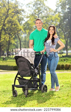 Vertical shot of young parents posing with their baby in a park on a sunny day - stock photo
