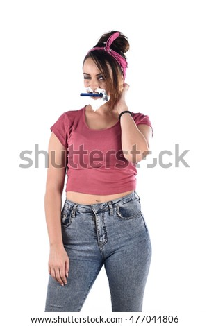 vertical studio portrait of a young woman with a beard made from shaving foam standing with a razor in her mouth