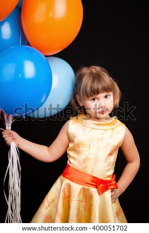 Vertical studio portrait of cute Caucasian blond little girl with colorful balloons - stock photo