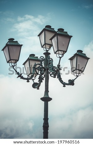 vertical, traditional street lamp with decorative metal flourishes - stock photo