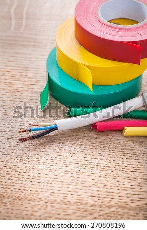 vertical view electric cable in corrugated pipe rolls of isulating tape heat shrinkable tubes on wooden board  - stock photo