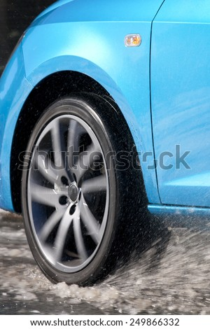 Vertical view of a car tire driving and splashing on the snow.  Driving on a snowy road. - stock photo
