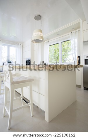 Vertical view of bright granitic kitchen island  - stock photo
