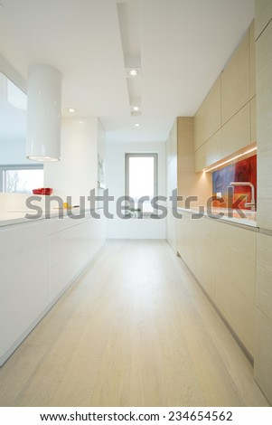 Vertical view of bright long kitchen interior - stock photo