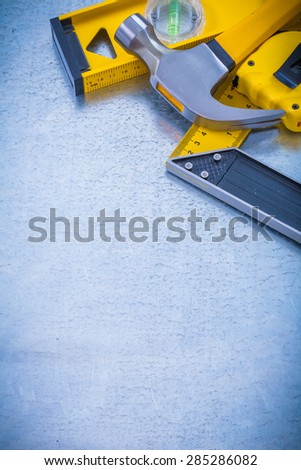 Vertical view of claw hammer tape measure construction level square ruler on metallic background maintenance concept
