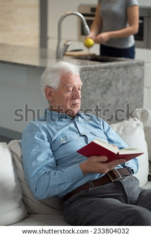Vertical view of senior man reading book - stock photo