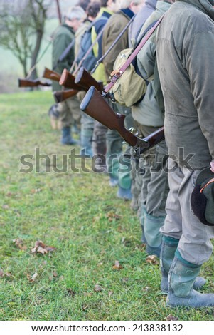 Vertical view of the gamekeepers standing in a row. - stock photo