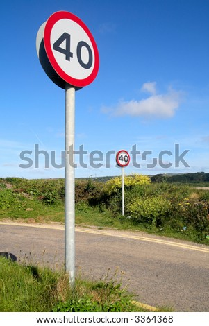 Vertical view of tow 40 miles an hour signs on a country lane. - stock photo