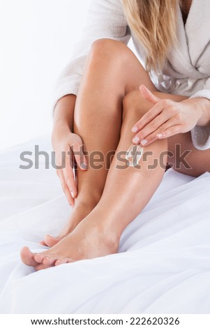 Vertical view of woman moisturizing her legs - stock photo
