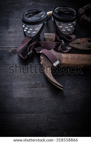 vertical view vintage tools goggles hammer pliers clamp. - stock photo