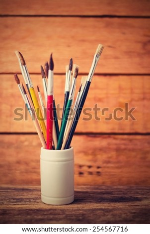 Vertical vintage retro photo of white jar full of old paintbrushes placed on old worn wooden board with next wood board in background. - stock photo
