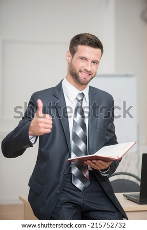 Vertical Waist-up portrait of handsome confident businessman in office interior holding a red notebook in his hands happy smiling looking at the camera and showing a sign OK - stock photo