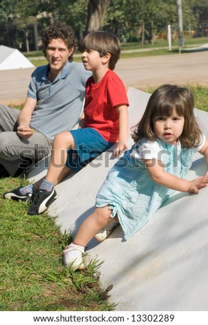 Vertically framed outdoor shot of a father, his son, and his daughter sitting in a park on a sunny day. - stock photo
