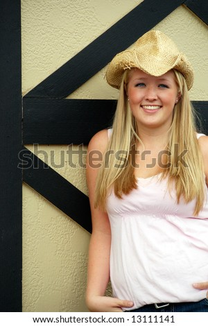 Vertically framed outdoor shot of a smiling teenage girl, with blond hair and blue eyes, standing next to barn door wearing a straw cowboy hat. - stock photo