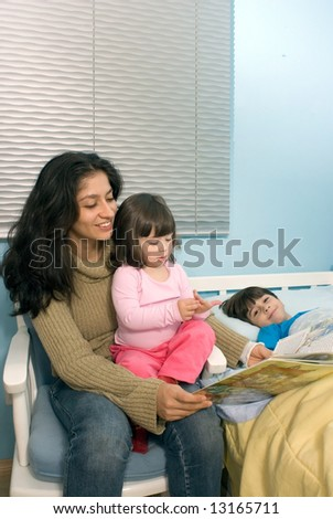 Vertically framed shot a smiling mother reading a book to a daughter sitting on her lap and son lying in bed. - stock photo