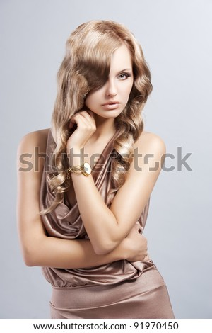 very alluring and attractive young blond woman in elegant silk dress and with old fashion hair style - stock photo