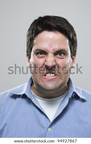 Very angry man in a blue shirt - stock photo