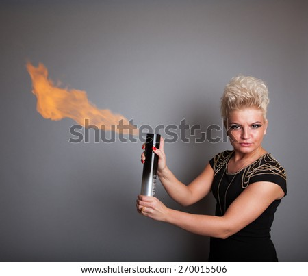 Very attractive and stylish professional hairdresser woman with flaming hair spray. With stylish blonde hair. In elegant outfit on grey background - stock photo