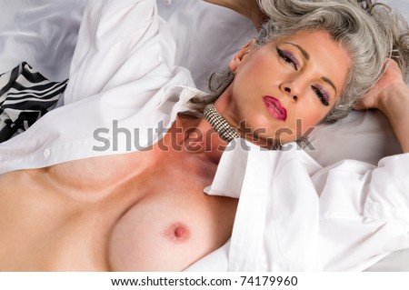 Very attractive woman at her fifities laying nude in bed. - stock photo