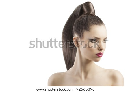very attractive young brunette with long hair and tail and creative hair style looking proud, she is turned of three quarters and looks down at left - stock photo
