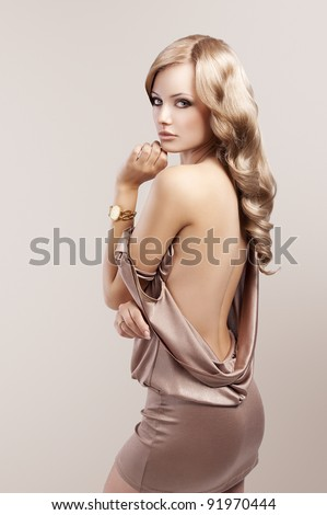 very beautiful and attractive young blond woman in elegant silk dress and with old fashion hair style and golden clock on wrist - stock photo