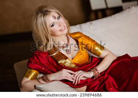 very beautiful and sensual blonde girl in Indian red Sari lying on the sofa - stock photo