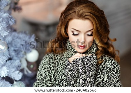 Very beautiful and sensual blonde girl with closed eyes in a grey knitted sweater on the background of the Christmas tree, close up - stock photo
