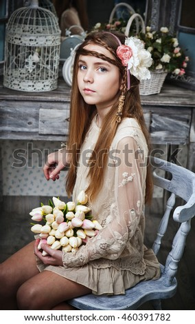 Very beautiful blonde young girl in a short dress vintage Provence sits on a white antique chair in front of a mirror. Keeps  Like a doll.