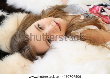 Very beautiful blonde young girl in It lies on the skin of a polar bear, laughing.