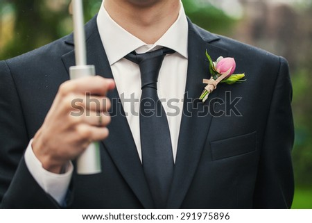 Very beautiful boutonniere on his jacket the groom