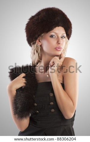 very beautiful fashion woman wearing an elegant black dress with boot and winter fur hat with stole on grey spotlight background - stock photo