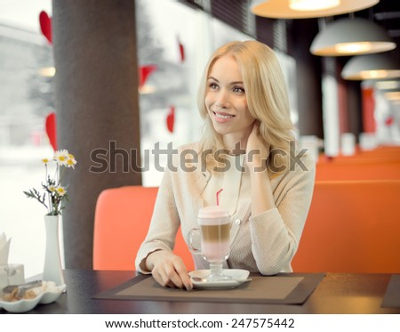 Very beautiful, happy,  young woman, sit in  Cafe and drink coffee- cocktail, horizontal portrait